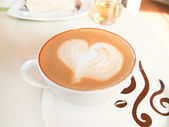 Cup of coffee with heart pattern in a white cup — Stock Photo