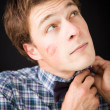 A fun young man with a trace of lipstick on his cheek — Stock Photo