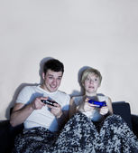 Young couple playing video games comfortably wrapped in a blanket. — Stock Photo