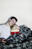 Ungt par tittar på TV. — Stockfoto