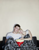 Young couple watching television and eating popcorn — Stok fotoğraf