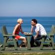 Romantic couple sitting on the beach — Stock Photo