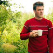 Young man in nature with a mug of coffee — Stock Photo