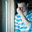 Tired young man by the window — Stock Photo
