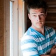 Young man at the window — Stock Photo #22694083