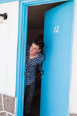 Young man looks out of the motel room — Stockfoto