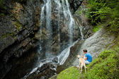 Young man with a dog near a waterfall — Stock Photo