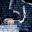 Hacker typing on a laptop - Stock Photo