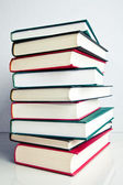 Stack of books on white reflective surface — Stock Photo