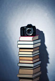 Camera on a high stack of books — Stock Photo