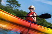 Woman With Safety Vest Kayaking Alone on a Calm River — Stock Photo