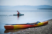 Kayak on the Sea Shore with Kayakers in the Background — Stock Photo