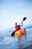 Woman With Safety Vest Kayaking Alone on a Calm Sea — Stock Photo