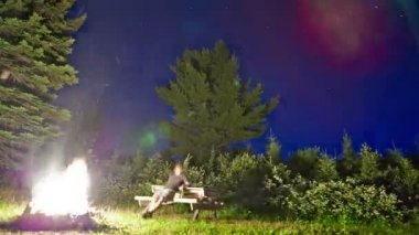 Stars Timelapse and lonely man in front of a campfire — Stock video