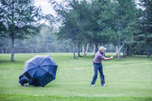 Golfer on a Rainy Day Swigning in the Fairway — Stock Photo
