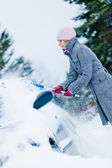 Woman Removing Snow from a Car with a Broom — Stock Photo