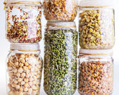 Stack of Different Sprouting Seeds Growing in a Glass Jar  — Stock Photo