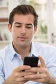 Young handsome man writting SMS on mobile phone. — Stock Photo