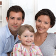 Smiling family portrait sitting in the living room at home — Stock Photo