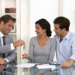 Real-estate agent giving keys to new property owners — Stock Photo #31456691