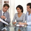 Financial consultant presents bank investments to a young couple — Stock Photo