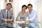 Happy young couple signing financial contract, looking camera — Stock Photo