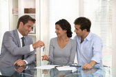 Real-estate agent giving keys to new property owners — Stock Photo