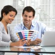 Happy couple choosing colours to paint new house — Stock Photo