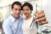 Happy smiling young couple showing a keys of their new house — Stock Photo