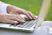Руки женщины, набрав на клавиатуре ноутбука, трава фон — Стоковое фото