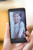 Woman hand with smartphone showing kid picture — Stock Photo