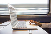 Close-up woman hands typing on a laptop keyboard in the train — Stock Photo