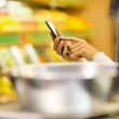 Woman using mobile phone while shopping in supermarket — Stock Photo