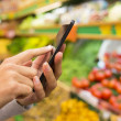 Woman using mobile phone while shopping in supermarket — Stock Photo #34163253