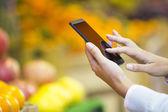 在超市购物时使用移动电话的女人 — 图库照片