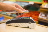 Woman paying with nfc technology on mobile phone, shopping, supe — Stock Photo