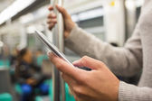 Woman using her cell phone on subway platform — Stock Photo