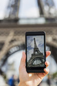 Woman in Paris taking pictures of the Eiffel Tower with her cell phone — Stock Photo