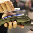 Man paying with NFC technology on mobile phone, in clothing stor — Stock Photo