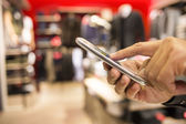 Close up of a man using mobile phone in clothing store — Stock Photo