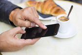 Man using a mobile phone on cafe terrace, croissant and coffee — Stock Photo