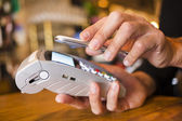 Man paying with NFC technology on mobile phone, in restaurant, b — Stock Photo