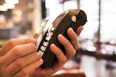 Man paying with NFC technology on credit card, in restaurant, ba — Stock Photo