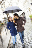 Couple with umbrella walking under rain — Stock Photo
