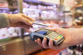Woman paying with NFC technology on mobile phone — Stock Photo