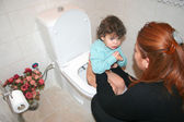 Mom puts the baby in toilet — Stok fotoğraf