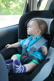 Baby in car seat for safety, looking outside — Stock Photo
