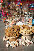 Natural sponges, souvenirs and shells on sale at street market — Stock Photo