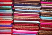 Folded scarfs at shelf as background — Stock Photo