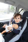 Pojke med sin docka i bilbarnstol för säkerhet — Stockfoto